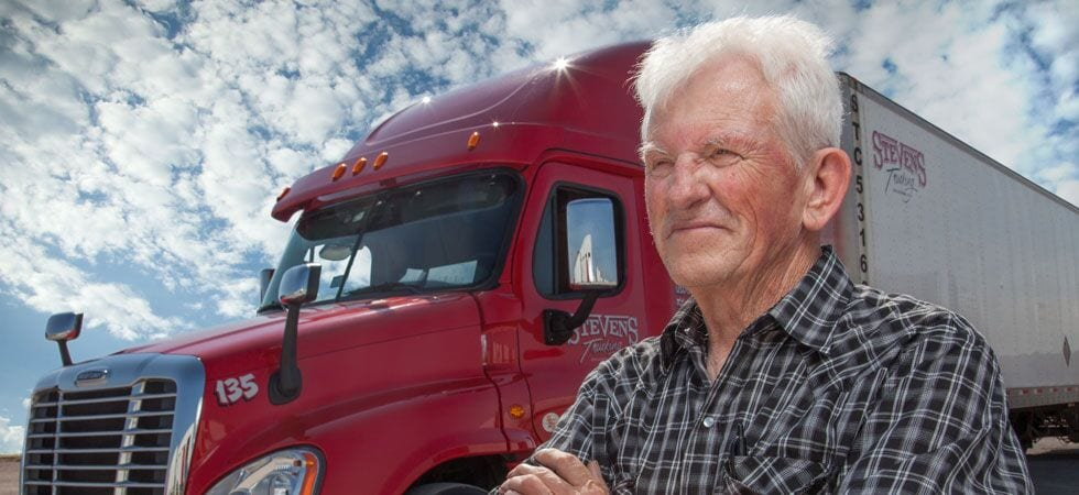 Older male truck driver standing in front of 18 wheeler truck